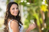 picture of glass water  - Pretty brunette drinking glass of water on a sunny day - JPG