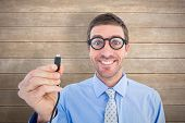 Geeky businessman holding a cable against wooden surface with planks