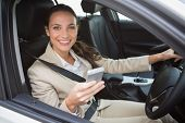Smiling businesswoman sending a text message in her car