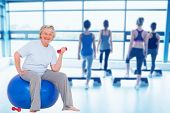 Composite image of senior woman sitting on exercise ball