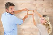 Attractive young couple hanging a frame against bleached wooden planks background
