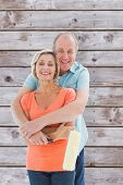 Happy older couple holding paint roller against wooden planks