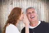 Woman telling secret to her partner against wooden planks background