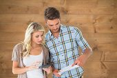 Attractive couple working out their finances against bleached wooden planks background