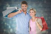 Attractive young couple holding shopping bags against black abstract light spot design