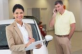Smiling businesswoman writing on clipboard at new car showroom