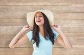 Happy young brunette wearing sunhat against wooden surface with planks