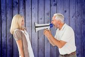 Angry man shouting at girlfriend through megaphone against wooden planks background