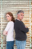Casual couple not speaking after fight against wooden background in pale wood