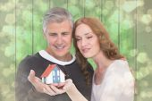 Casual couple holding small house against light glowing dots design pattern