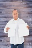 Serious man holding torn sheet of paper against faded grey wooden planks