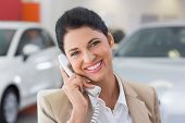 Smiling businessman making a phone call at new car showroom