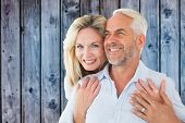 Smiling couple embracing with woman looking at camera against wooden background in blue