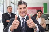 Smiling business team standing while one giving thumbs up at new car showroom