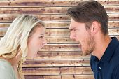 Angry couple shouting during argument against wooden planks background