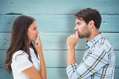Upset young couple not talking against painted blue wooden planks