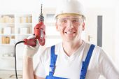 Smiling man with electric drill wearing protective helmet and glasses