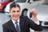 Smiling salesman giving a customer car key at new car showroom