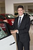 Smiling businessman showing a car for sale at new car showroom