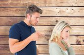 Young couple having an argument against wooden planks background