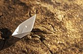 Paper ship on the dried ground
