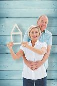 Happy older couple holding house shape against wooden planks