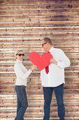 Older affectionate couple holding red heart shape against wooden planks