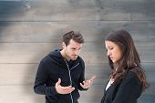 Unhappy brunette listening to boyfriend against bleached wooden planks background