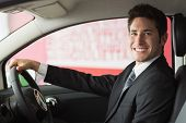 Smiling businessman at the wheel sitting in a car for sale at new car showroom