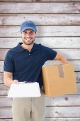 Happy delivery man with cardboard box and clipboard against wooden planks