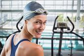 Pretty swimmer by the pool smiling at camera against cross trainer machines overlooking large swimming pool