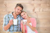 Attractive young couple sitting holding mugs against bleached wooden planks background
