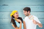 Happy young couple painting together and laughing against painted blue wooden planks