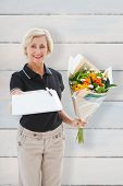 Happy flower delivery woman looking for signature against wooden planks