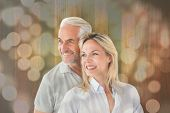 Happy couple smiling and embracing against light circles on bright background