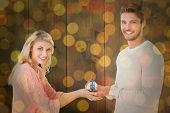 Attractive couple holding miniature house model against close up of christmas lights