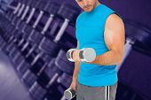 Mid section of a fit man exercising with dumbbells against heavy black dumbbells on rack in weights room