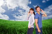 Couple both making phone calls against green field under blue sky