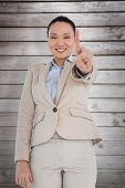Smiling asian businesswoman pointing against wooden planks