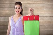 Portrait of pretty brunette showing shopping bags against wooden surface with planks