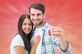 Happy young couple holding new house key against red abstract light spot design
