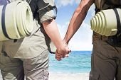 Hitch hiking couple standing holding hands on the road against beach scene