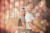 Happy couple holding moving boxes against light circles on black background