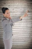 Unsmiling thinking asian businesswoman pointing against wooden planks background