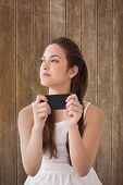 Thoughtful brunette holding her phone against wooden planks background