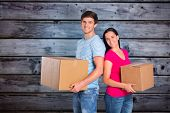 Young couple holding moving boxes against grey wooden planks