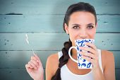 Pretty brunette having cup of tea against painted blue wooden planks