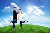 Smiling couple with raised legs against green hill under blue sky
