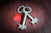 Keys with decorative heart on wooden background