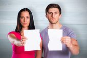 Couple showing broken piece of paper against bleached wooden planks background